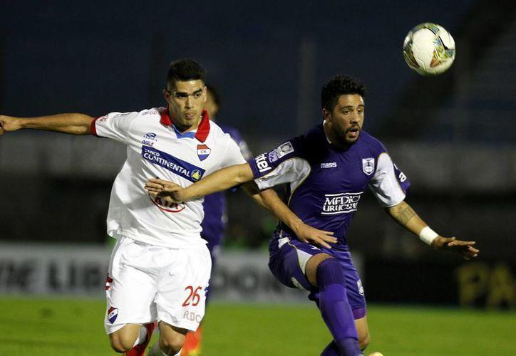El jugador de Nacional de Paraguay, Brian Montenegro (i), disputa el balón con Ramón Arias (d), de Defensor Sporting de Uruguay, en la semifinal de la Copa Libertadores de América en el estadio Centenario, en Montevideo. (EFE)