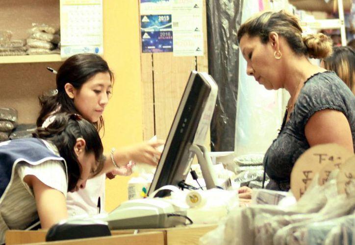 Opinan que se debe motivar al empleado con incentivos. Imagen de un contexto de un par de empleadas que atienden a una cliente, en el centro de Mérida. (Milenio Novedades)