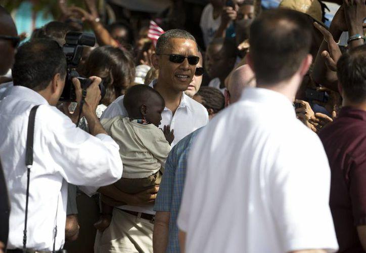 El presidente Barack Obama sostiene un bebé después de tomar un tour de la isla de Goree. (Agencias)