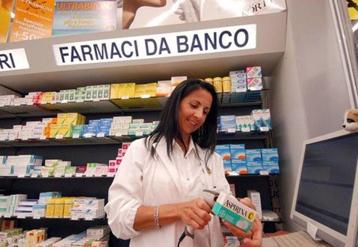 Imagen de una empleada farmacéutica al checar el precio de una caja de Aspirinas, que por cierto previene el cáncer de próstata. (Ansa)