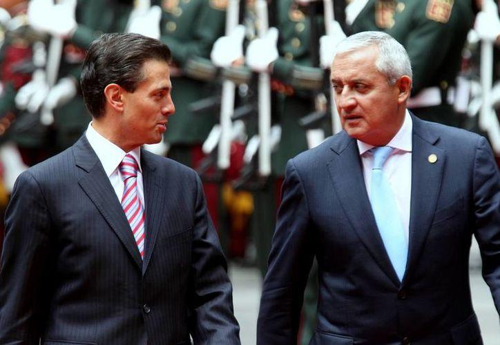 El presidente de México, Enrique Peña Nieto, intercambia comentarios con su par de Guatemala, Otto Pérez Molina, al darle la bienvenida al país. (Notimex)