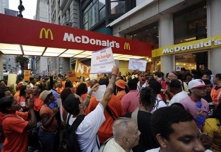Los trabajadores realizan una protesta fuera de un restaurante McDonald en la Quinta Avenida de Nueva York. (Agencias)