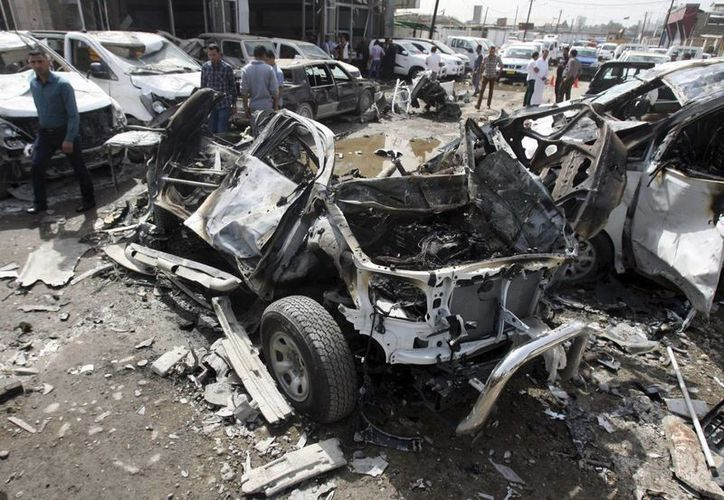 Civiles examinan el concesionario donde fue perpetrado un ataque con bomba, en el distrito Nahda, en Bagdag, Irak, este viernes. (EFE)