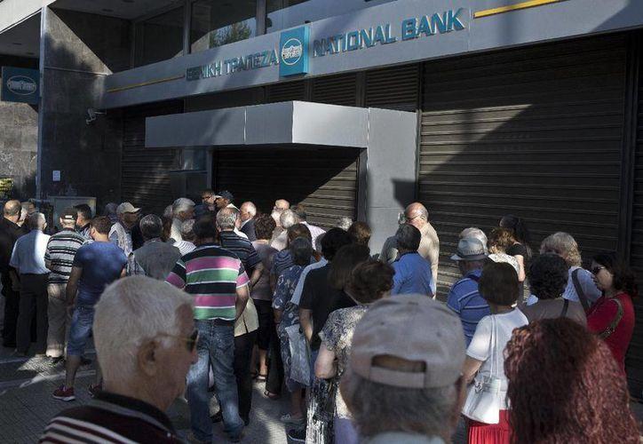 Un grupo d eancianos, que suele cobrar sus pensiones a final de mes, hacen cola ante una sucursal bancaria cerrada en Atenas, el 29 de junio de 2015. (Foto AP/Petros Giannakouris)