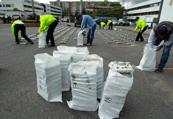 Integrantes de la policía colombiana guardan paquetes de cocaína luego de exhibirlos a los medios de comunicación en Bogotá, Colombia. (EFE)