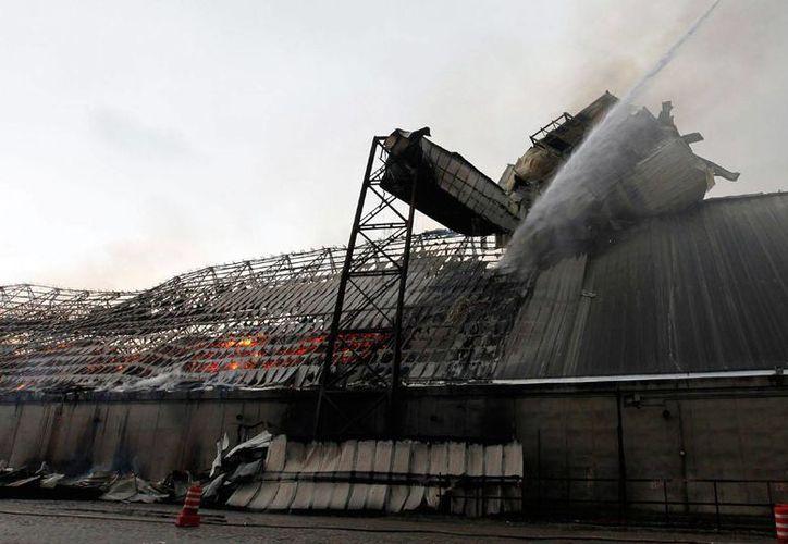 Los bomberos requirieron de 10 pipas de agua para combatir el fuego en el almacén de Cosan, en el puerto de Santo, Brasil. (Detalle Foto: Reuters/elhorizonte.mx)