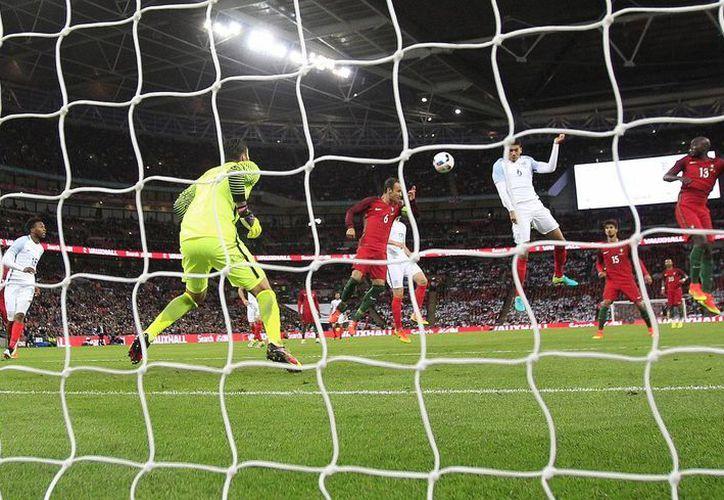 Chris Smaling al momento de cabecear para dar a Inglaterra la victoria al final del partido amistoso contra Portugal, previo a la Eurocopa. (AP)