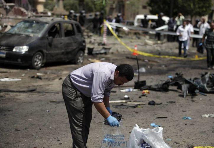 Un oficial de seguridad egipcio reúne evidencias en la escena del ataque contra el ministro. (Agencias)