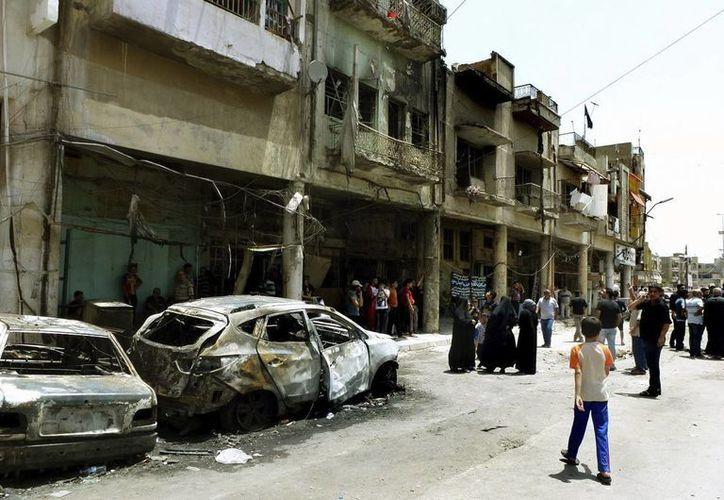 Varias personas caminan por el lugar donde se produjo una explosión en el distrito de Saadon en Bagdad, Irak. (EFE)