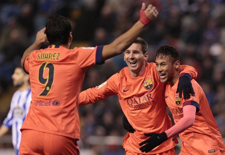 Messi celebra uno de los tres goles que anotó para el Barcelona frente al Deportivo La Coruña. (AP)