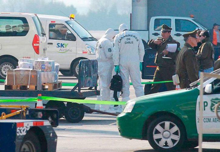 Carabineros (policía militarizada) de Chile revisan la zona donde se cometió un asalto. Los ladrones se llevaron entre 7.5 y 10 mdd, una cantidad 'histórica' para una hurto en el país sudamericano. (Efe)