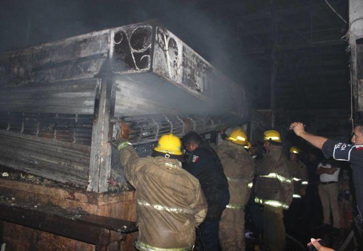 """Los bomberos tardaron aproximadamente una hora en apagar el incendio en la zona conocida como Tianguis II del mercado municipal de Mérida """"Lucas de Gálvez"""", en la Noche Vieja de 2015. (Oficial)"""