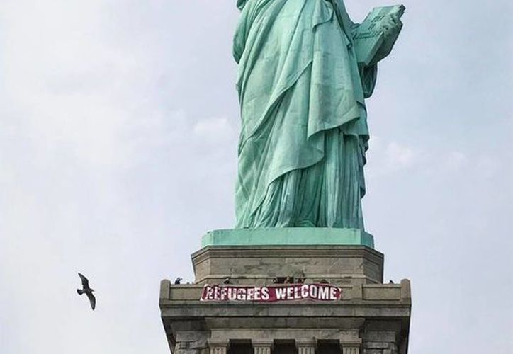 """En esta foto de Vitória Londero, una pancarta gigante apareció ayer en el pedestal de la Estatua de la Libertad con la frase """"Refugiados Bienvenidos"""", este martes en Nueva York. (Vitória Londero vía AP)"""