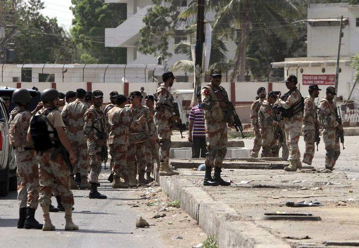 Agentes de las Fuerzas de Seguridad paquistaníes examinan el lugar en el que fue detonada una bomba, en Karachi, Pakistán. (EFE)