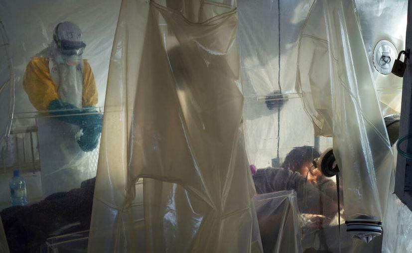 En esta fotografía del sábado 13 de julio de 2019, trabajadores de salud con vestimenta protectora revisan a un paciente aislado en un pequeño cubículo hecho con plásticos en un centro de atención del ébola en Beni, República Democrática del Congo. (AP Foto/Jerome Delay)