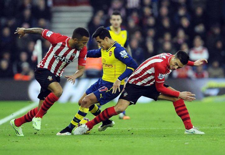Alexis Sánchez (c), del Arsenal, pelea por el balón con Ryan Bertrand (i) y Dusan Tadicin (d), del Southampton, durante el partido de la Premie. (EFE)