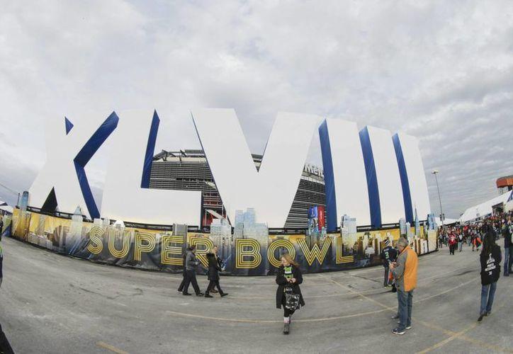 Aficionados caminan frente a un letrero por el XLVIII Super Bowl entre los Broncos de Denver y los Seahawks de Seattle en el estadio MetLife en East Rutherford, New Jersey. (EFE)