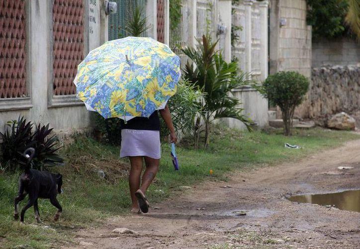Para el sol o la lluvia, se recomienda hoy cargar con el paraguas. (Juan C. Albornoz/SIPSE)