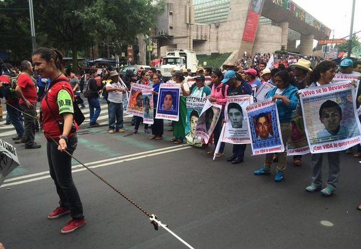 Una valla de personas de la Plataforma de Solidaridad por Ayotzinapa resguarda a los familiares de los estudiantes. (twitter/@Reporte_Indigo)