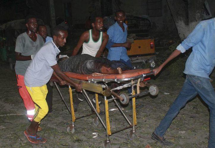 Varias personas transportan a uno de los heridos tras el ataque con coche bomba contra un céntrico hotel de la capital en Mogasdiscio, Somalia, hoy 1 de junio de 2016. (EFE)
