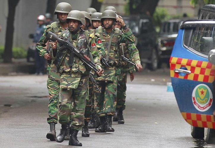 Soldados de Bangladesh salen de la zona donde se encuentra un restaurante popular entre los extranjeros, atacado por un grupo de milicianos fuertemente armados. (Agencias)