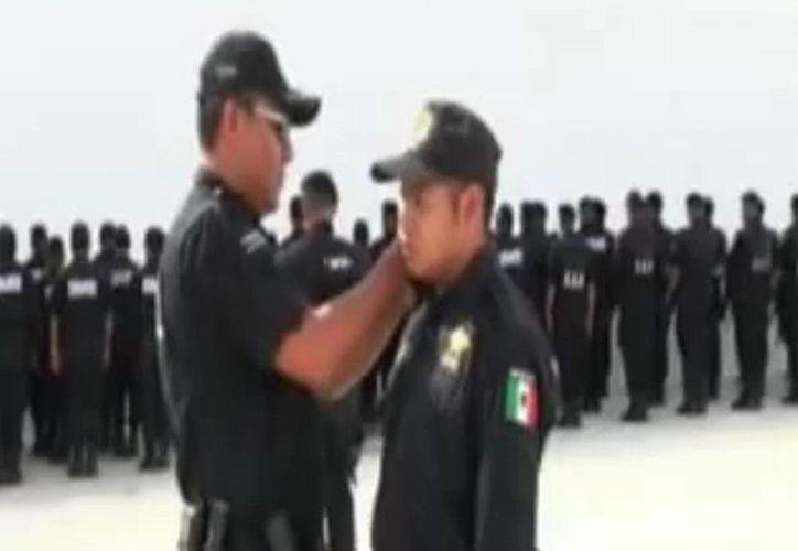 Captura de pantalla del video que la SSP difundió ayer vía YouTube, en el que se puede ver la degradación de uno de los policías destituidos.