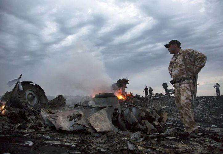 Un militar observa los restos del Boeing 777-200 caído en Ucrania con 295 pasajeros a bordo. (AP)