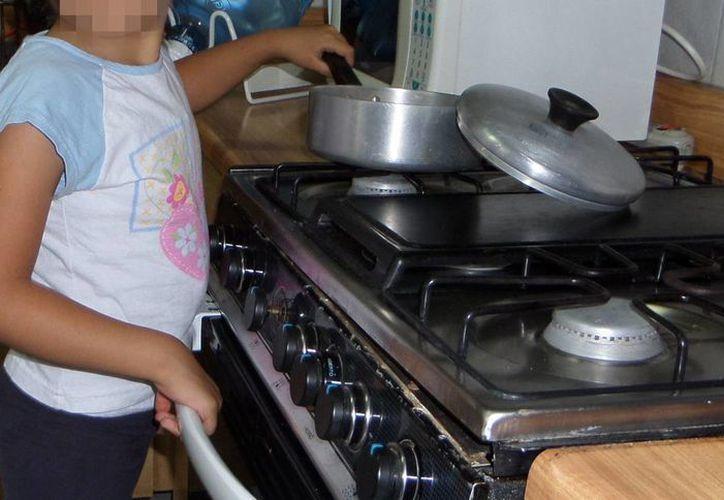 Recomiendan a los padres de familia vigilar a los menores en la cocina, ya que los descuidos pueden ser fatales. Imagen de una niña agarrando una olla que está en una estufa. (Imagen tomada de salud.morelos.gob.mx)