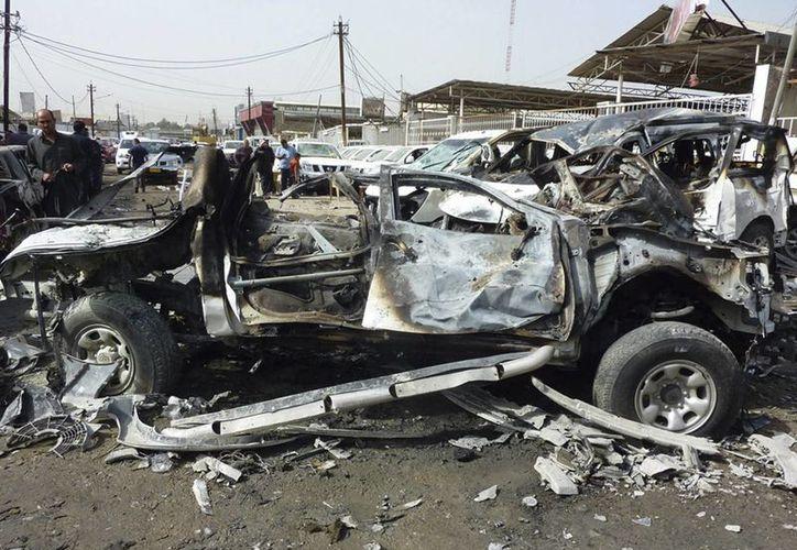 Civiles pasan por delante de un concesionario donde fue perpetrado un ataque con bomba, en el distrito Nahda, en Bagdag. (EFE)