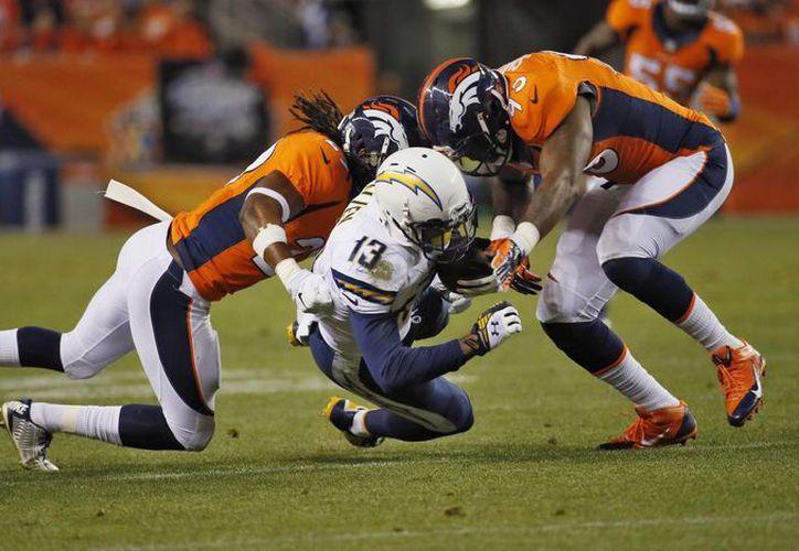 El receptor de Chargers, Keenan Allen (13) es golpeado por Quanterus Smith (d) y Bradley Roby, de Broncos, en la primera mitad del partido de NFL.(Foto: AP)
