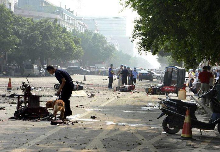 Varios investigadores buscan evidencias en el lugar tras la explosión registrada cerca de una escuela de primaria en Lingchuan, China. (EFE)