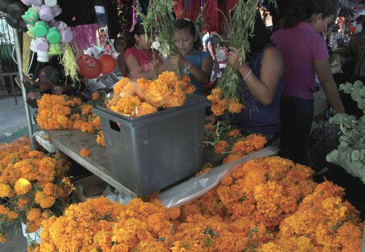 Entre los productos que más se venden, están las flores y los dulces típicos. (Tomás Álvarez/SIPSE)