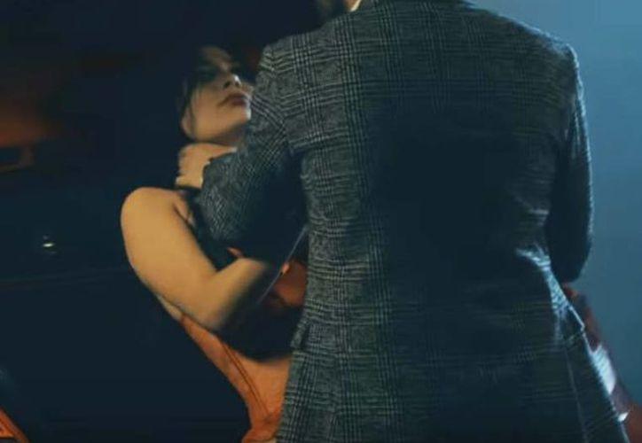 En la foto, la escena en que Gerardo Ortiz intenta dañar a la dama del videoclip. (Captura de pantalla)
