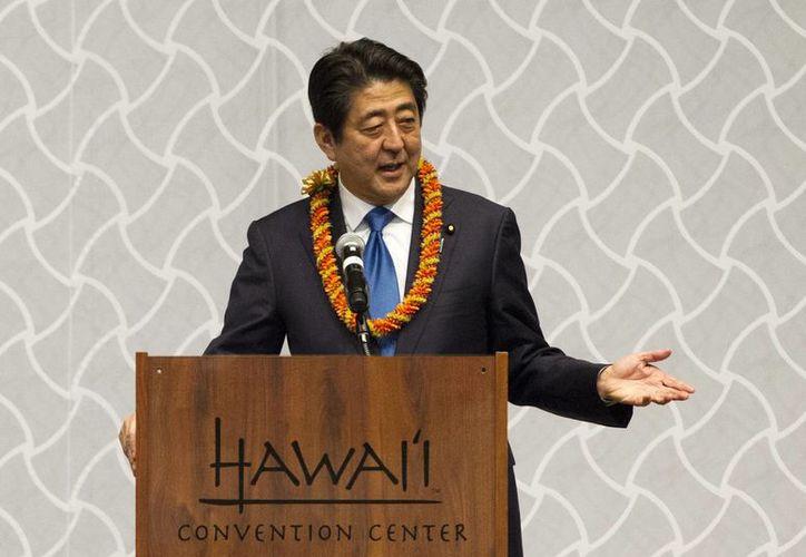 El primer ministro japonés Shinzo Abe habla en una cena en su honor en Honolulu. Abe visitará Pearl Harbor, cuyo bombardeo en 1941 provocó la entrada de EU en la Segunda Guerra Mundiaal. (AP/Marco Garcia)