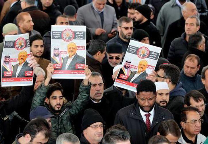 Tres hombres sostienen imágenes del periodista opositor saudí Yamal Jashogi. (Foto: EFE)