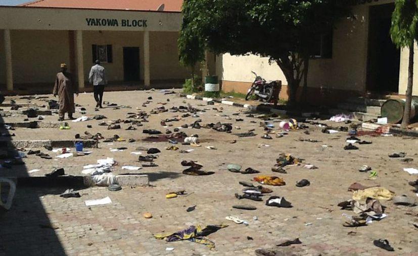 Agentes de seguridad nigerianos y miembros de la Cruz Roja, inspeccionan la zona donde el 7 de julio explosionó una bomba en Zaria, al norte de Nigeria. El atentado de hoy fue perpetrado por una mujer con discapacidad mental. (EFE/Archivo)