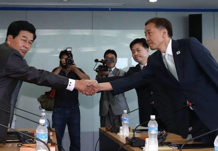 El director general del Distrito Inter Coreano, Kim Ki-Woong (d), saludando a su homologo de Corea del Norte, Park Chul-Soo (i), antes de reunirse en el complejo industrial de Kaeseong. (EFE/KOREA POOL)