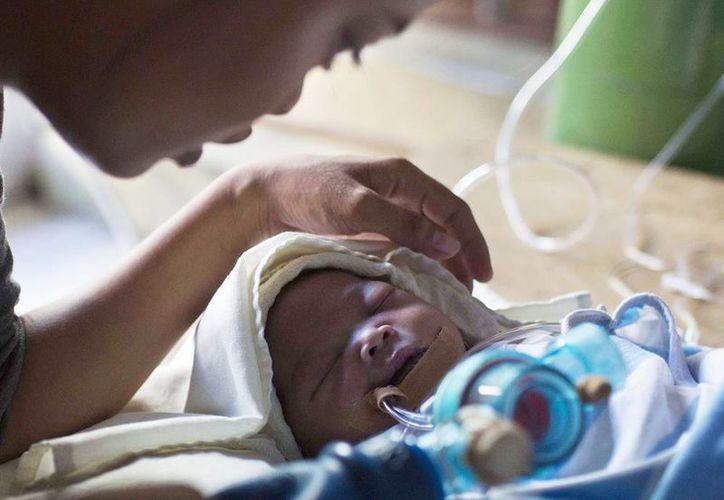 Genia Mae Mustacisa bombea con la mano oxígeno hacia los pulmones de su hija de tres días de nacida en una capilla católica en el interior del Centro Medico Regional de Bisayas Orientales, en la ciudad de Taclobán, Filipinas. (Agencias)