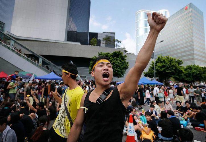 Un manifestante lanza consignas contra el Gobierno, en Hong Kong, en donde las protestas suben de tono: dieron un plazo de apenas 24 horas para que renuncie el jefe del Gobierno, Leung Chun-Ying. (AP)