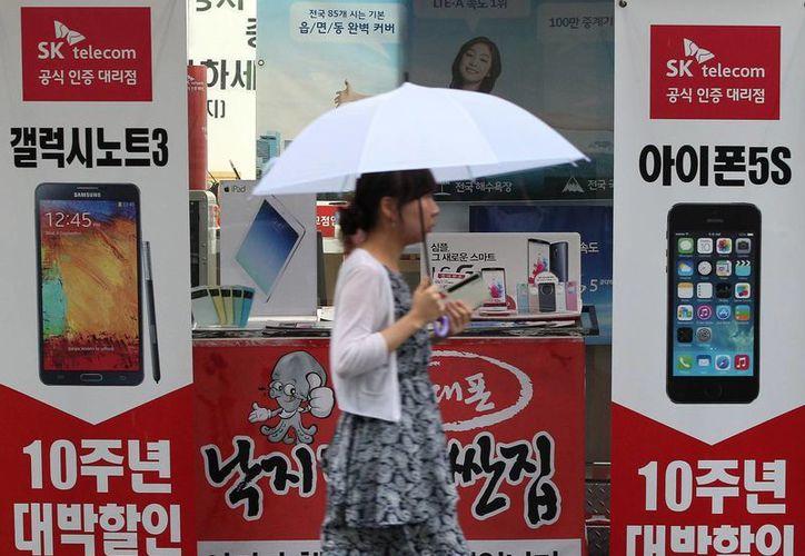 Una mujer camina por carteles publicitarios de Samsung Electronics 'Galaxy Note III y del iPhone 5s de Apple en una tienda de telefonía móvil en Seúl, Corea del Sur. (Agencias)