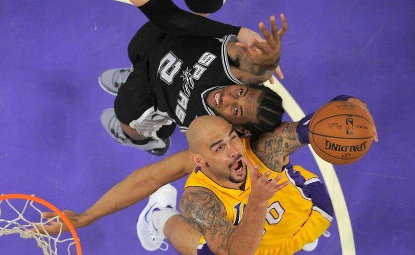 Robert Sacre (debajo), de Lakers, y Kawhi Leonard, de Spurs, batallan por un rebote en la segunda mitad del partido entre sus equipos. (Agencias)