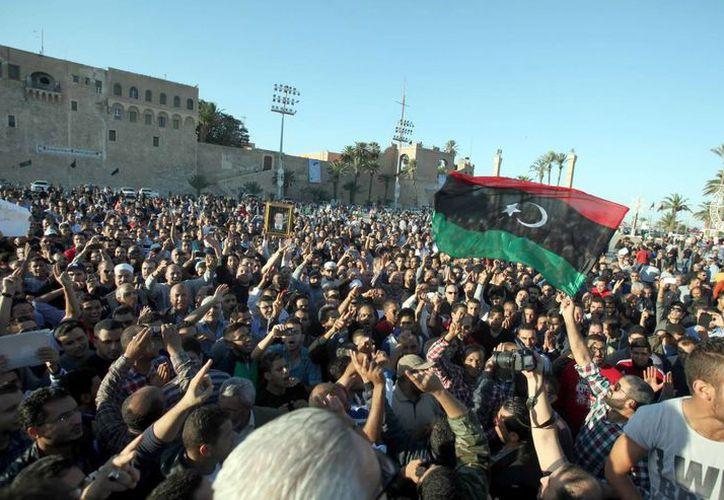 Manifestantes con una bandera libia durante los funerales de los manifestantes muertos el viernes en Trípoli. (EFE)