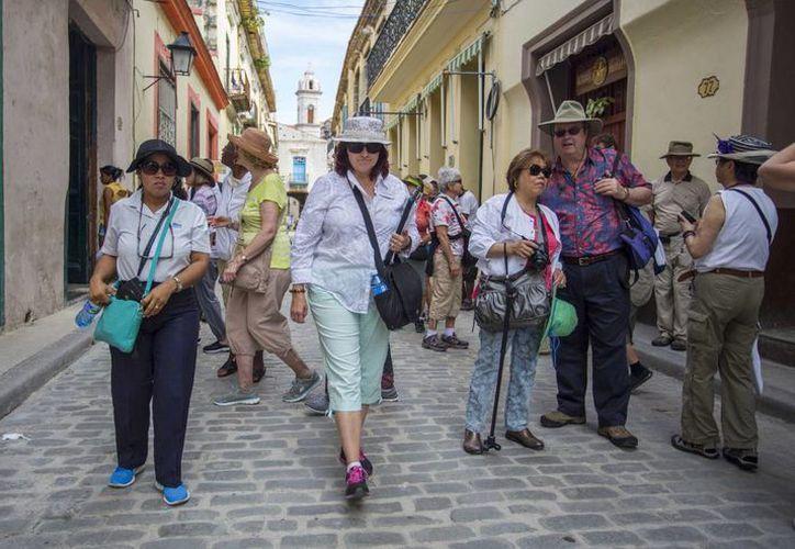La directora de la agencia turística smarTours Pamela Boudrot (c) y la guía local Enedis Tamayo conducen a un grupo de turistas durante un recorrido de La Habana. (Agencias)