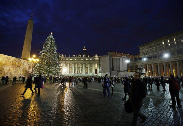 Cuando la noche caía sobre la Plaza de San Pedro se encendieron las luces que adornan el árbol. (Agencias)