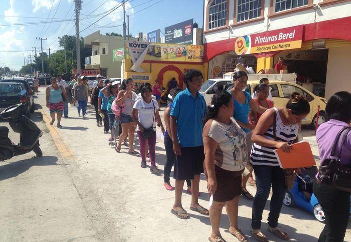 Cientos de padres de familia forman largas filas para inscribir a sus hijos al siguiente curso escolar.  (Luis Ballesteros/SIPSE)