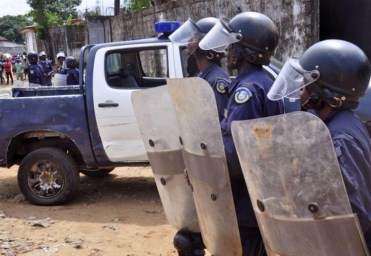 Policías liberianos antimotines vigilan un camino principal después que un grupo de gente bloqueó un camino principal después que el cadáver de una víctima del ébola no fue retirado por los trabajadores de salud en Monrovia, Liberia. (Agencias)