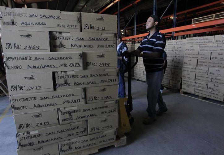 Empleados del Tribunal Supremo Electoral de El Salvador trabajan en el traslado de paquetes electorales los cuales serán distribuidos en San Salvador. (EFE)