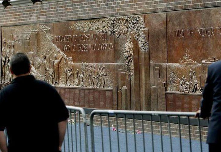 Dos miembros del departamento de bomberos de la Ciudad de Nueva York observan el monumento en honor a los 343 bomberos que murieron en los ataques terrorista del 11 de septiembre de 2001. (EFE)