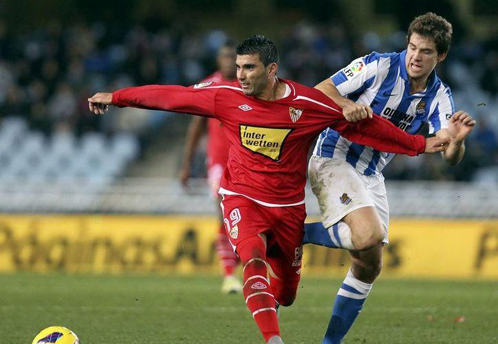 El defensa de la Real Sociedad, Íñigo Martínez (d), lucha por el balón con José Antonio Reyes, centrocampista del Sevilla. (EFE)