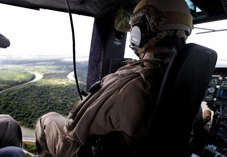 Un piloto de la Oficina de Aduanas y Control Fronterizo sobrevuela con su helicóptero el río Bravo tratando de detectar actividades ilegales en la frontera entre México y Estados Unidos. (Agencias)